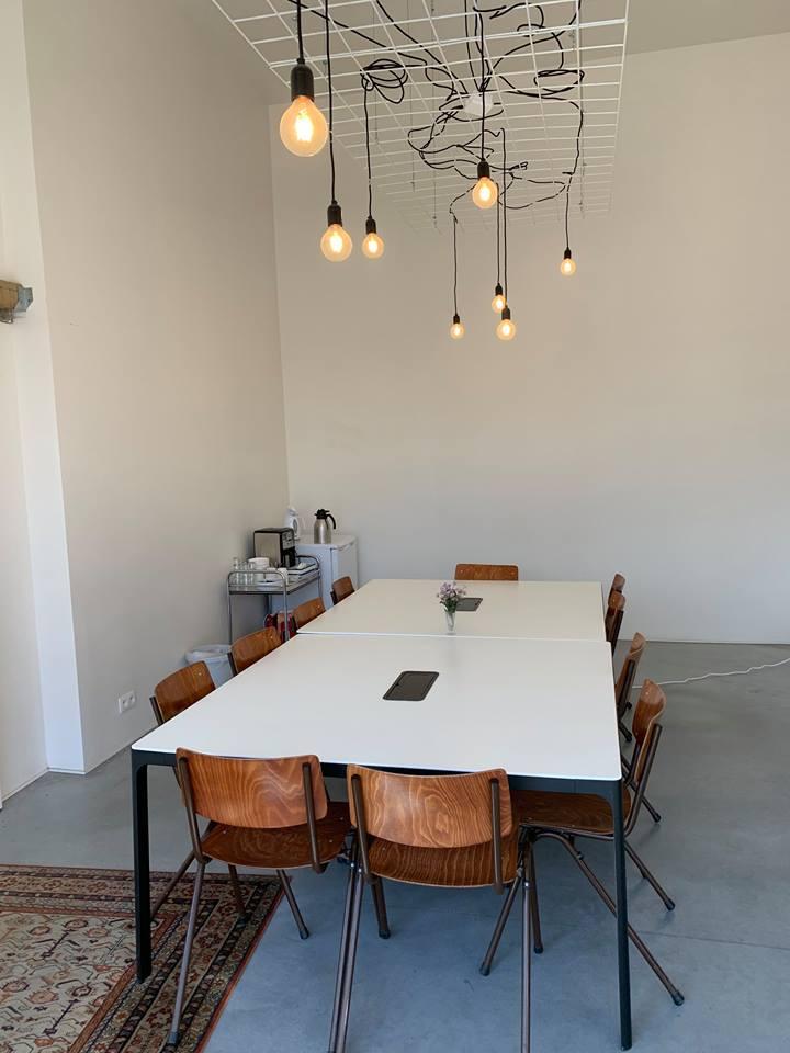 Kleine zaal met 11 stoelen rond een centrale tafel en koelkast in de hoek