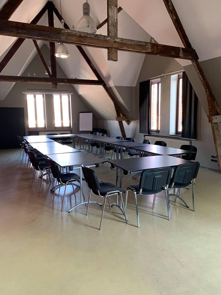 Zaal met 12 tafels en whiteboard onder de nok van het dak