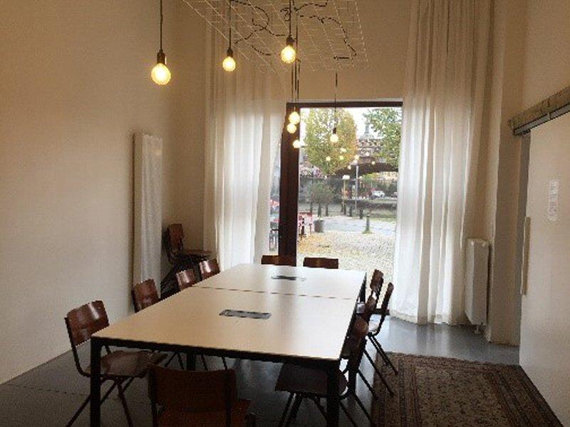 Kleine zaal met 11 stoelen rond een centrale tafel op het gelijkvloers uitkijkend op de Draakplaats